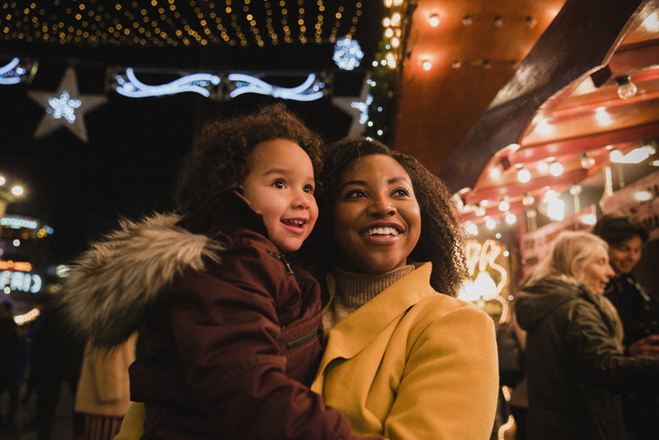 African American woman and her child, looking at Christmas lights